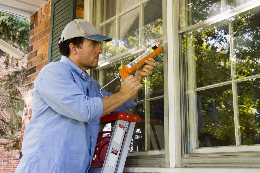 Man caulking the outside of a house's windows