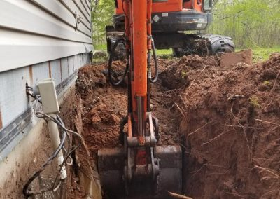 Digging down to the footing to place drain tile